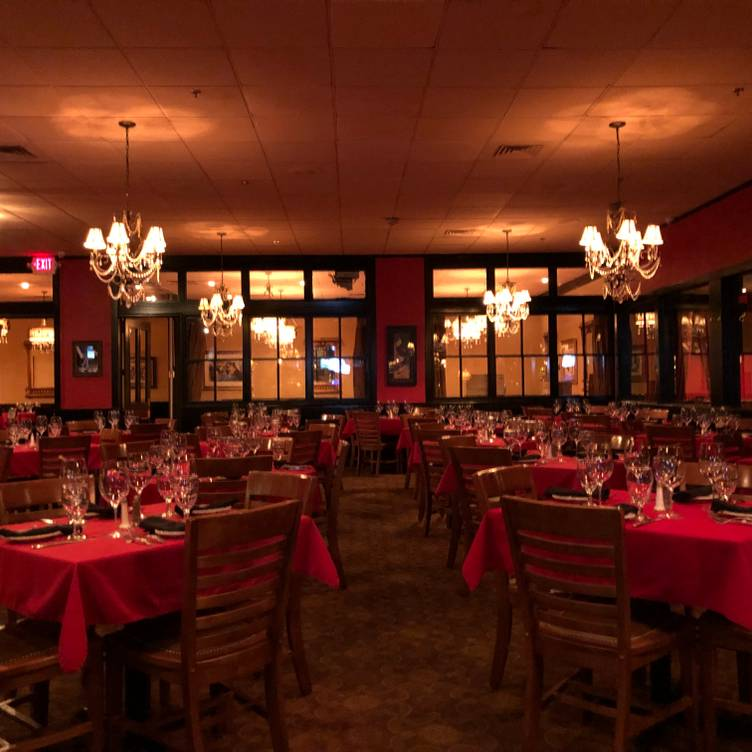 a room of tables and chairs. Tables have wine glasses and napkins set out on red table cloths.