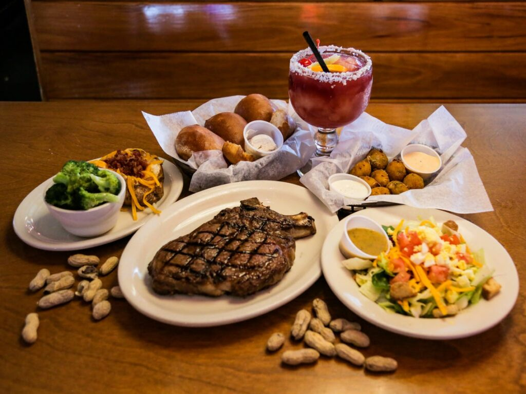 plate of steak with a side of fried okra, baked potatoes, broccoli, salad and peanuts. Served with a drink.