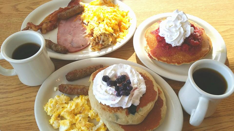 one plate with eggs, ham, bacon, and sausage. Another plate has pancakes with whip cream, eggs, and sausage. two cups of coffee.