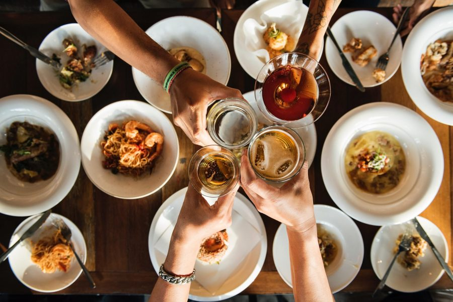 A table of food and plates being eaten. four arms reached out, making a toast.