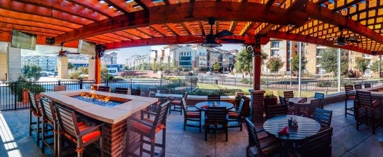 Outdoor seating under a wooden patio. tables and chairs. One of the tables has a fire pit in the middle.