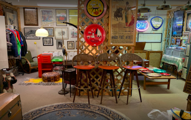 room filled with antique chairs, neon signs, rugs, picture frames, and poster signs.