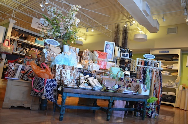 Table filled with purses, scarfs, jewelry, and wallets on a display in Hollyhocks