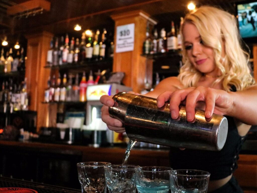 Blonde girl pouring blue shots at a bar in Lubbock