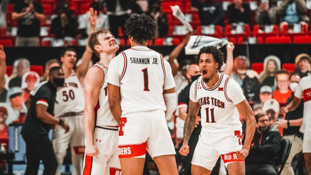 Texas Tech basketball players Terrance Shannon Jr, Kyler Edwards, and Mac McClung celebrate after a play during a game