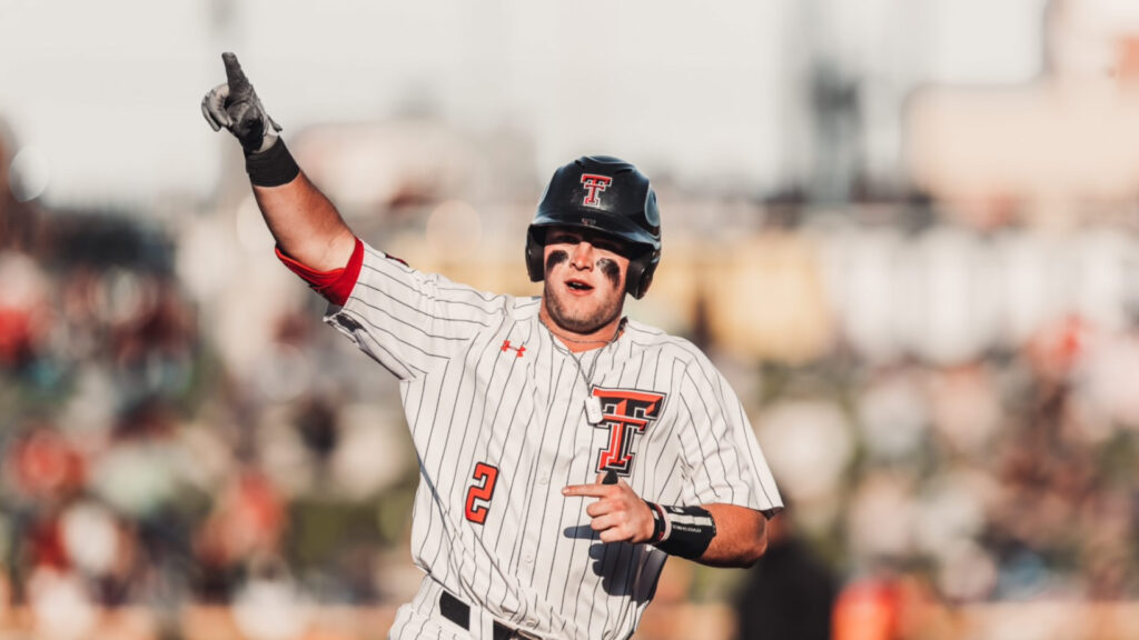 Texas Tech player Jace Jung points to the sky as he is is running on the field  with a batting helment.